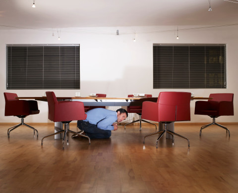 Man hiding under boardroom table