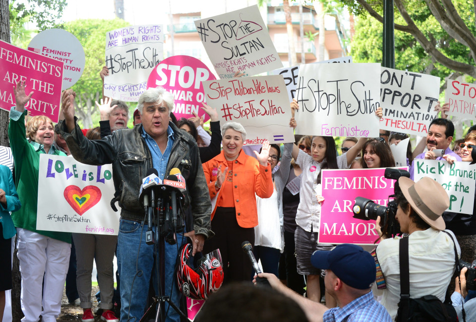 Jay Leno speaks at a gathering of Women's Rights and LGBT groups protesting across from the Beverly Hills Hotel, owned by the Sultan of Brunei, demanding he rescind a Taliban-like Brunei penal code which included the stoning to death of gay men and lesbians and the public flogging of women who have abortions, on May 5 2014 in Beverly Hills, California. The southeast Asian nation of Brunei, a would-be member of the Obama administrations Trans Pacific Partnership (TPP) agreement, is under fire from Hollywood and human rights activists for adopting a brutal penal code based on Sharia law with punishments including flogging, dismemberment and death by stoning for crimes such as adultery and sodomy.