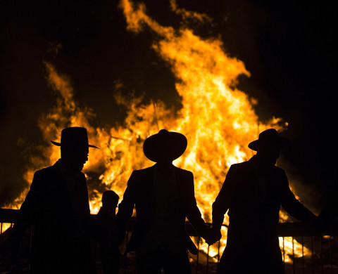 Ultra Orthodox Jews are silhouetted against a bonfire during celebrations for the Jewish holiday of Lag Ba'Omer in Kfar Chabad, near the city of Lod, May 17, 2014. The holiday, which marks the end of a plague in the Middle Ages that killed thousands of disciples of a revered rabbi in the holy land, is celebrated by lighting bonfires across the country. REUTERS/Amir Cohen (ISRAEL - Tags: RELIGION TRAVEL SOCIETY ANNIVERSARY) - RTR3PN7L