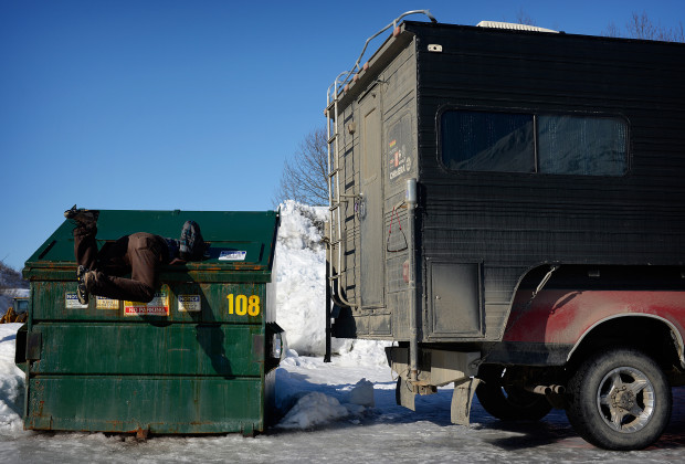 Joey Howell digs in a dumpster for cardboard to help get the truck unstuck on March 24, 2014 in the port town of Valdez, Alaska.  Howell and James Roh experienced numerous mechanical issues of various scopes on their journey, including losing traction in an icy parking lot.  JAMES ROH