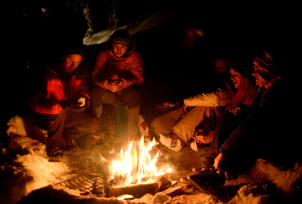 Joey Howell, left, and Harald Vedo Tveit, center, enjoy a camp fire with French skiers at Whitewater Resort near Nelson, British Columbia on Feb. 17, 2014.  While living in the parking lot of the resort, Howell and James Roh met skiers and snowboarders from all over the world traveling to sample the snow of British Columbia.     JAMES ROH