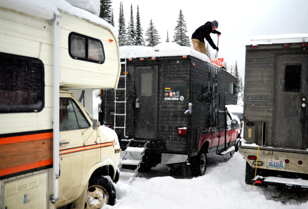 Joey Howell clears snow off the top of the camper during a storm at Whitewater Resort near Nelson, British Columbia on Feb. 13, 2014.  Howell and James Roh spent over a week parked in the lot, snowboarding the mountains in the canyon, and meeting visitors to the area.      JAMES ROH