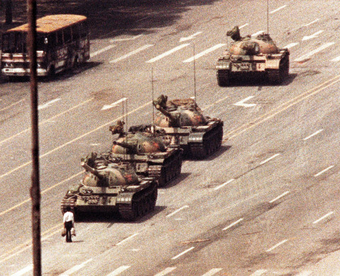 A man stands in front of a convoy of tanks in the Avenue of Eternal Peace in Beijing, June 5, 1989. REUTERS/Arthur Tsang  AS - RTRLY4L