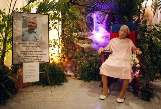 The body of Georgina Chervony Lloren, who died of natural causes on Sunday at the age of 80, is propped up in a rocking chair during her wake in a funeral home in San Juan, Puerto Rico, Monday, May 26, 2014. Miriam Chervony, daughter of Georgina, explained that her mother had asked her family that in the case of her death, she wanted her funeral to be in her favorite rocking chair and in her wedding gown from her second marriage 32 years ago. (AP Photo/Ricardo Arduengo)