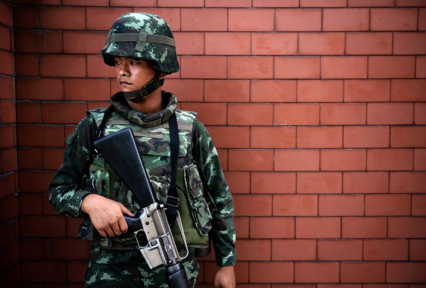 A Thai soldier stands outside the Government Public Relations Department after martial law was imposed in Bangkok on May 20, 2014.    Thailand's army on May 20 declared martial law across the crisis-gripped kingdom to restore order following months of anti-government protests that have left 28 people dead and hundreds wounded.   AFP PHOTO/Christophe ARCHAMBAULT        (Photo credit should read CHRISTOPHE ARCHAMBAULT/AFP/Getty Images)