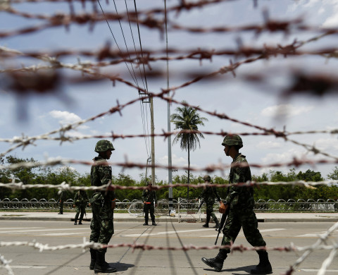 "Thai soldiers man a checkpoint near pro-government ""red shirt"" supporters encampment in suburbs of Bangkok May 20, 2014. Thailand's army declared martial law nationwide on Tuesday to restore order after six months of street protests that have left the country without a proper functioning government, but denied that the surprise move amounted to a military coup. REUTERS/Damir Sagolj (THAILAND - Tags: SOCIETY CIVIL UNREST MILITARY POLITICS) - RTR3PXNT"