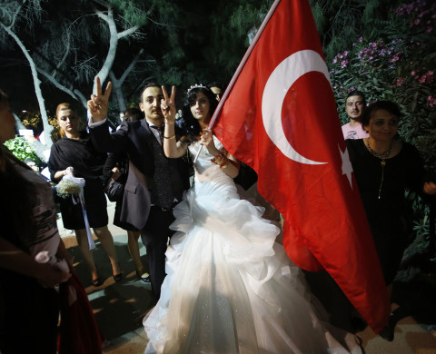 Ayse Diskaya (R), her son Mazlum (3rd R) and daughter-in-law Sureyya (C) visit Gezi Park near Taksim Square after the couple's wedding ceremony in Istanbul June 9, 2013. Diskaya, a 48-year-old housewife who lives in a poor neighbourhood of Istanbul with her husband and two sons, has joined the anti-government protest in Istanbul's Gezi Park. She is both an active member of the left-wing cultural association Halkevleri and a women's rights activist, who has devoted herself to women's issues for many years. Now she is taking part in the anti-government protest movement because she says she thinks changes brought in under Prime Minister Tayyip Erdogan threaten modern, secular society in a way that will have a negative impact on women. Picture taken June 9, 2013. REUTERS/Murad Sezer (TURKEY - Tags: POLITICS CIVIL UNREST SOCIETY TPX IMAGES OF THE DAY)  ATTENTION EDITORS: PICTURE 19 OF 19 FOR PACKAGE  'TAKSIM - ONE WOMAN'S PROTEST' SEARCH 'AYSE DISKAYA' FOR ALL IMAGES - RTX10LA5