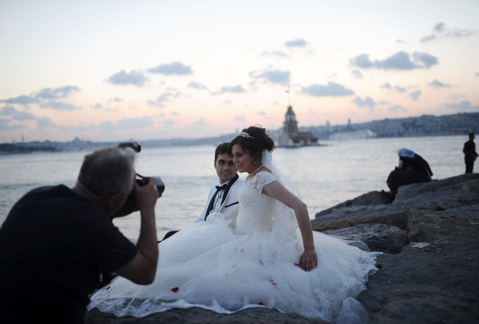 A newly married couple poses for their wedding pictures in front of The Maiden's Tower in Istanbul. T
