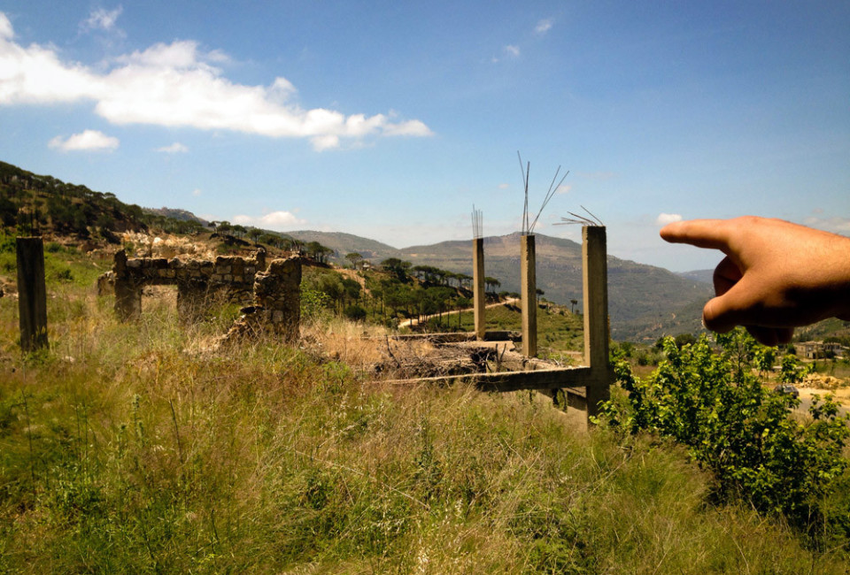 Elie Lahoud points to buildings on his family's property destroyed during Lebanon's ciivl war.