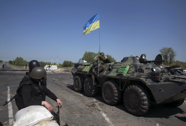 A Ukrainian soldier climbs on top of an armoured personnel carrier at a checkpoint near the town of Slaviansk in eastern Ukraine May 4, 2014.