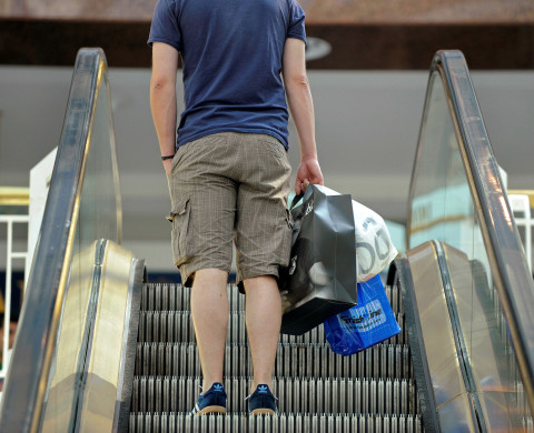 A shopper carrying bags takes the escalator at the Pentagon City Shopping Mall in Arlington, Virginia.- RTR27VQR