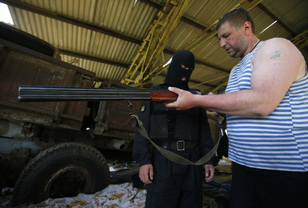 Members of the pro-Ukrainian militia group calling themselves the Donbass Battalion prepare a weapon at a military base they had set up in the small town of Velika Novosyolka, in the Dontesk.