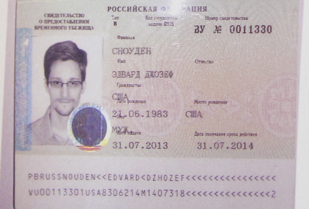Fugitive former U.S. spy agency contractor Edward Snowden's new refugee documents granted by Russia is seen during a news conference in Moscow August 1, 2013. Snowden slipped quietly out of the airport on Thursday after securing temporary asylum in Russia, ending more than a month in limbo in the transit area.  REUTERS/Maxim Shemetov (RUSSIA - Tags: POLITICS CRIME LAW) - RTX127IL