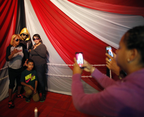 Lidianette Carmona, behind right, the wife of the late boxer Christopher Rivera, stands with Rivera's mother Celines Amaro, left, and Rivera's son Julio Christopher, as they pose for photos taken by fans with the body of Christopher Rivera propped up in a fake boxing ring during his wake at the community recreation center within the public housing project where he lived in San Juan, Puerto Rico, Friday, Jan. 31, 2014. Elsie Rodriguez, vice president of the Marin funeral home, explained that Rivera had asked his family that if he died, he wanted his funeral to make reference to his boxing career. (AP Photo/Ricardo Arduengo)