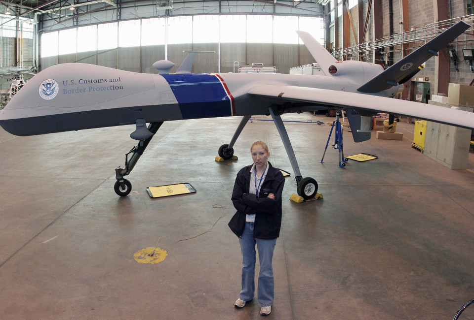 Pilot Cassandra Hunt stands in front of the MQ-9 Predator B in its' hanger at Fort Huachuca Arizona, Decmeber 5, 2006. The drone, with a wing span of 66 feet and a maximum altitude of 50,000 feet, is used to detect undocumented immigrants entering the United States along illegally along the border with Mexico. REUTERS/Jeff Topping (UNITED STATES) - RTR1K5CX