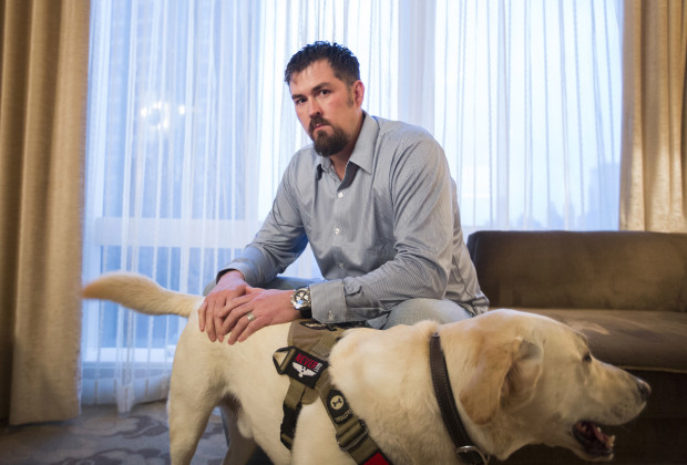 "Former U.S. Navy SEAL Marcus Luttrell poses for a portrait with his dog Mr. Rigby while promoting the film ""Lone Survivor"" in New York, December 5, 2013."