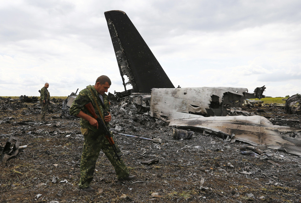 Pro-Russian separatists walk at the site of the crash of the Il-76 Ukrainian army transport plane in Luhansk, June 14, 2014. Pro-Russian separatists shot down a Ukrainian army transport plane with an anti-aircraft missile killing all 49 military personnel on board.