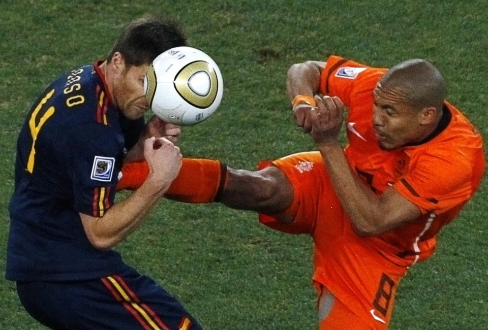 Spain's Xabi Alonso (L) gets a boot in his chest by Netherlands' Nigel de Jong as they fight for the ball during their 2010 World Cup final soccer match at Soccer City stadium in Johannesburg July 11, 2010.