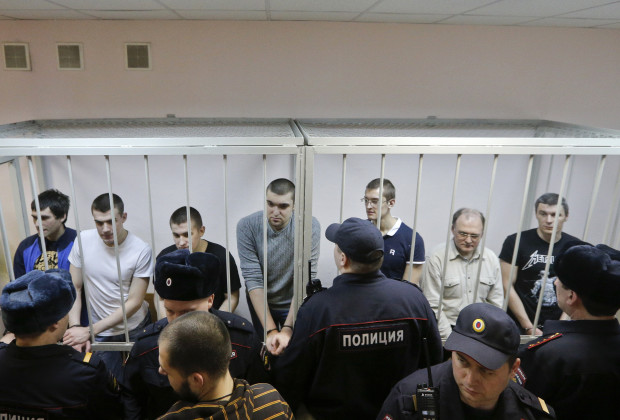 "Defendants in the ""Bolotnaya"" case stand in a holding cell as they wait for their sentencing during a court hearing in Moscow February 24, 2014. Russian police detained several protesters chanting ""Freedom"" on Monday outside a Moscow courthouse where a judge was expected to sentence eight defendants convicted of attacking police at an anti-government demonstration in 2012. REUTERS/Maxim Shemetov (RUSSIA - Tags: POLITICS CRIME LAW) - RTX19E7S"
