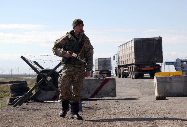 A Ukrainian soldier stands guard at a check point at the border between Ukraine and Crimea near the Salkovo village, on March 18 , 2014. Ukraine stood stunned on March 18, 2014 after Russia claimed Crimea and both sides suffered their first casualties that threatened to see the worst East-West crisis since the Cold War spin out of control. AFP PHOTO/ SERGIY GUMENYUK        (Photo credit should read SERGIY GUMENYUK/AFP/Getty Images)