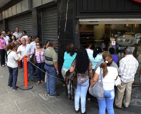 People line up to buy goods at a store in Caracas on March 10, 2014. Protesters in Venezuela have been venting their anger over the soaring crime rate, high inflation, a shortage of food and commodities.  AFP PHOTO / LEO RAMIREZ        (Photo credit should read LEO RAMIREZ/AFP/Getty Images)