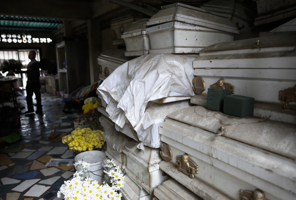 A worker makes a floral arrangement next to coffins at an undertaker's showroom in Caracas in June 2014. Venezuelan funeral homes are struggling to find coffins. (