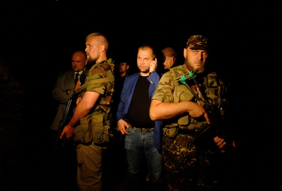 """Self-proclaimed Prime Minister of the pro-Russian separatist """"Donetsk People's Republic"""" Alexander Borodai (C) stands as he arrives on the site of the crash."""