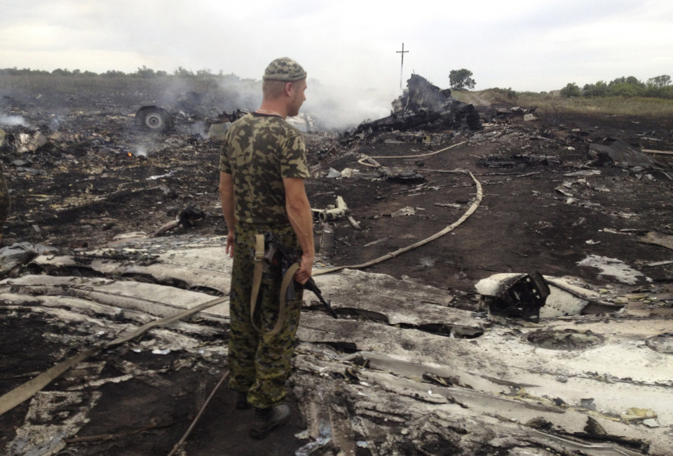 An armed pro-Russian separatist stands at a site of a Malaysia Airlines Boeing 777 plane crash in the settlement of Grabovo in the Donetsk region, July 17, 2014.