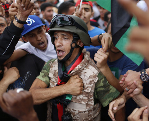 "People demonstrate together with a soldier in support of Khalifa Haftar's ""Operation Dignity"", a campaign against Islamists, at Martyrs' Square in Tripoli."