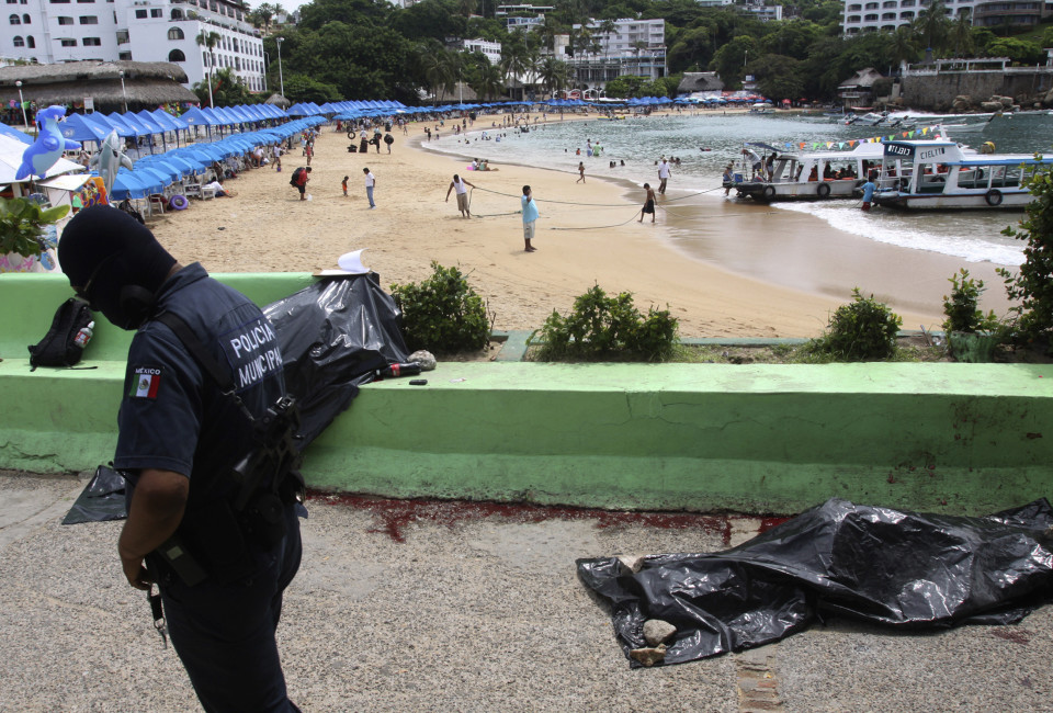 A police officer walks near dead bodies lying on a street facing the beach at the Mexican resort of Acapulco.