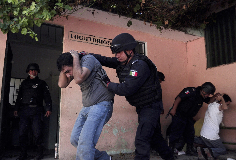 Policemen transfer inmates to another area after a shooting in the Tuxpan prison in Iguala, in the Mexican State of Guerrero.