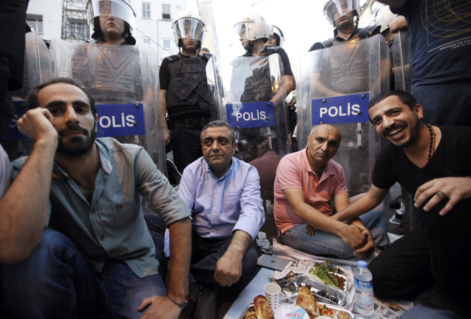People prepare to break their fast on the first day of the holy month of Ramadan in front of police officers .