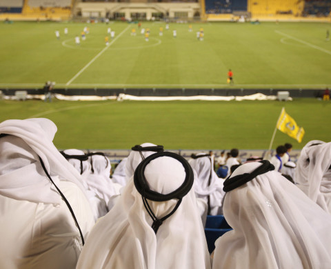 Fans wearing traditional local dress attend the Gharafa vs. Kharaitiyat Qatar Stars League football match at Al Gharafa Stadium.