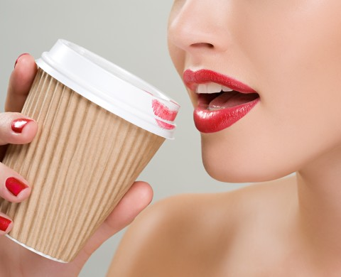 Woman drinking coffee from a paper cup --- Image by © Image Source/Corbis