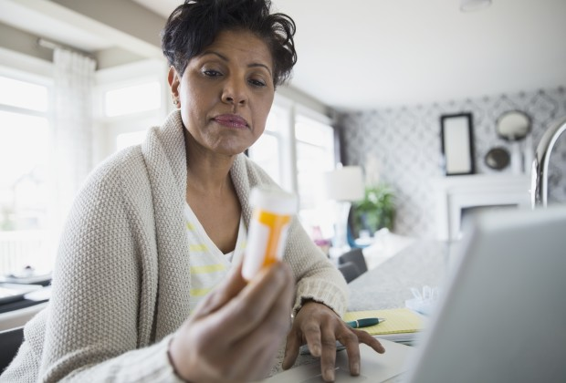 02 May 2014 --- Woman reading prescription bottle label at laptop --- Image by © Hero Images Inc./Hero Images Inc./Corbis