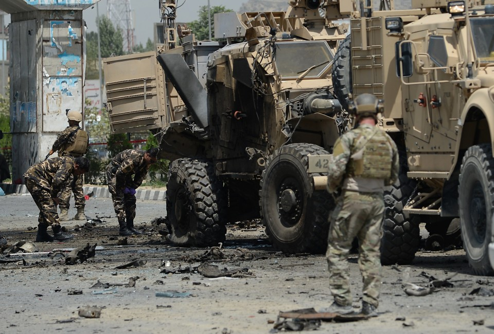 US soldiers part of NATO-led International Security Assistance force (ISAF) and Afghan security forces inspect the wreckage of an armored vehicle at the site of a suicide attack in Kabul on August 10, 2014. A suicide attacker targeted a NATO convoy in Kabul on August 10, killing four civilians and wounding at least 35 others, officials said, in the latest violence to hit the capital as politicians wrangle over election results. The NATO force made no immediate comment on the attack, which came as foreign troops rapidly wind down combat operations at the end of a 13-year war against Taliban insurgents. AFP PHOTO/SHAH Marai        (Photo credit should read SHAH MARAI/AFP/Getty Images)