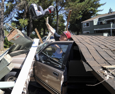 Karl Luchsinger removes a child's car seat from a vehicle after a carport collapsed after a 6.1 earthquake struck Napa, California on Sunday, August 24, 2014. More than 80 people were injured after the quake caused fires, significant structure damage, water main breaks, and power outages throughout the region. AFP PHOTO/JOSH EDELSON        (Photo credit should read Josh Edelson/AFP/Getty Images)