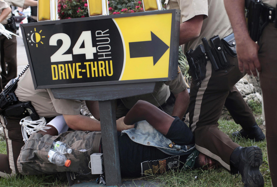 Police officers detain a demonstrator for protesting against the fatal shooting of Michael Brown in Ferguson, Missouri August 18, 2014. Missouri Governor Jay Nixon lifted the curfew for the St. Louis suburb of Ferguson on Monday and began deploying National Guard troops to help quell days of rioting and protests spurred by the fatal shooting of the black unarmed teenager by a white policeman.     REUTERS/Joshua Lott (UNITED STATES - Tags: CRIME LAW CIVIL UNREST TPX IMAGES OF THE DAY) - RTR42VIL
