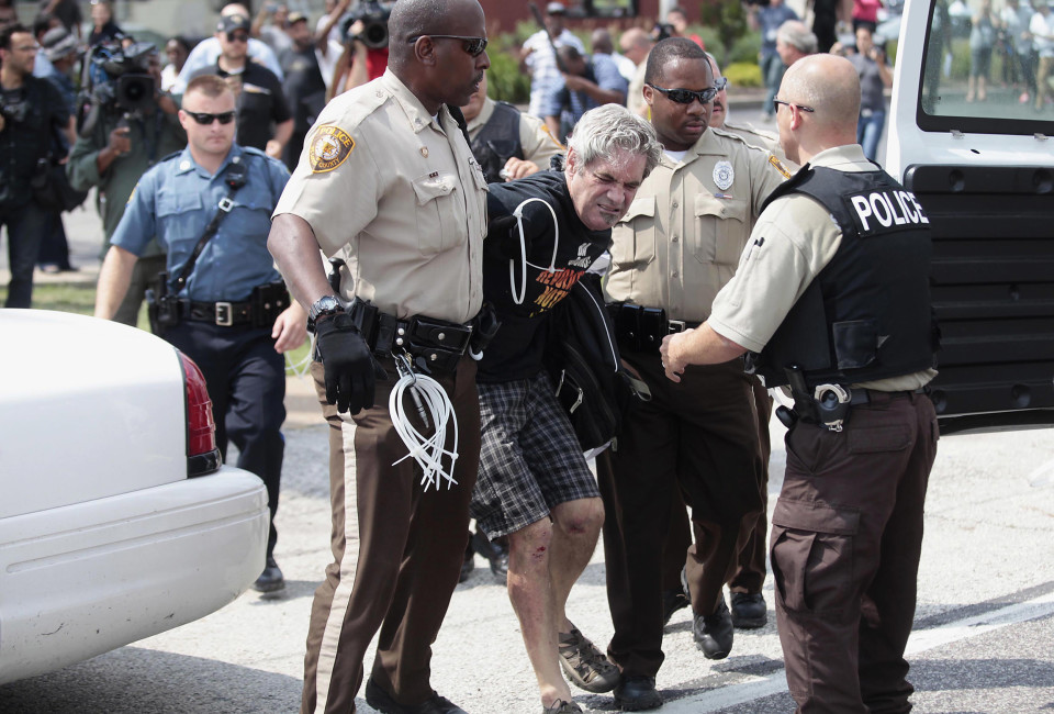 Police officers detain a demonstrator for protesting against the fatal shooting of Michael Brown in Ferguson, Missouri August 18, 2014. Missouri Governor Jay Nixon lifted the curfew for the St. Louis suburb of Ferguson on Monday and began deploying National Guard troops to help quell days of rioting and protests spurred by the fatal shooting of the black unarmed teenager by a white policeman.    REUTERS/Joshua Lott (UNITED STATES - Tags: CRIME LAW CIVIL UNREST TPX IMAGES OF THE DAY) - RTR42VGQ