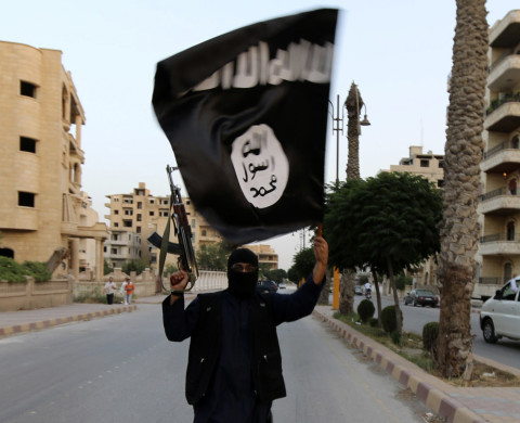 "A member loyal to the Islamic State in Iraq and the Levant (ISIL) waves an ISIL flag in Raqqa June 29, 2014. The offshoot of al Qaeda which has captured swathes of territory in Iraq and Syria has declared itself an Islamic ""Caliphate"" and called on factions worldwide to pledge their allegiance, a statement posted on jihadist websites said on Sunday. The group, previously known as the Islamic State in Iraq and the Levant (ISIL), also known as ISIS, has renamed itself ""Islamic State"" and proclaimed its leader Abu Bakr al-Baghadi as ""Caliph"" - the head of the state, the statement said. REUTERS/Stringer (SYRIA - Tags: POLITICS CIVIL UNREST TPX IMAGES OF THE DAY) - RTR3WBPT"