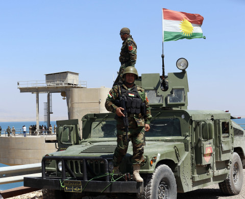 "Peshmerga fighters stand on a vehicle with a Kurdish flag as they guard Mosul Dam in northern Iraq August 21, 2014. Despite its structural faults, the country's biggest dam at 3.6 km long, built by a German-Italian consortium in the 1980s, is a vital water and power source for Mosul, Iraq's largest northern city of 1.7 million residents. Control the dam and you control the 'keys' to the city. With that in mind, Islamic State insurgents who captured swathes of Iraq and Syria and declared a caliphate, wrested control of the dam from Kurdish forces in recent weeks. While Iraqi and Kurdish forces recaptured the dam with the help of U.S. air strikes on Monday, ""the most dangerous dam in the world"" - as a U.S. Army Corps of Engineers report described it - still has the potential for catastrophe.   REUTERS/Youssef Boudlal (IRAQ - Tags: CIVIL UNREST POLITICS MILITARY TPX IMAGES OF THE DAY) - RTR437KH"