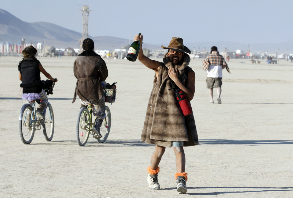 A Burning Man participant toasts the sunrise with a bottle of champagne at the 2013 Burning Man arts and music festival in the Black Rock desert of Nevada, August 30, 2013. The Burning Man organization received approval from the federal government to have a maximum of 68,000 participants attend the festival.  REUTERS/Jim Bourg  (UNITED STATES - Tags: SOCIETY) FOR USE WITH BURNING MAN RELATED REPORTING ONLY. FOR EDITORIAL USE ONLY. NOT FOR SALE FOR MARKETING OR ADVERTISING CAMPAIGNS. NO THIRD PARTY SALES. NOT FOR USE BY REUTERS THIRD PARTY DISTRIBUTORS - RTX1328T