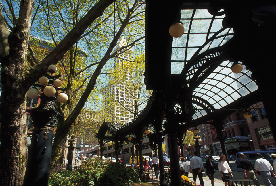 ca. 1991, Seattle, Washington State, USA --- People walk beneath an ornate glass and metal shelter in historic Pioneer Square. The shelter was built in 1905 and renovated in 1973; it originally led to underground public restrooms which are no longer operational. Seattle, Washington, USA. --- Image by © Mike Zens/CORBIS