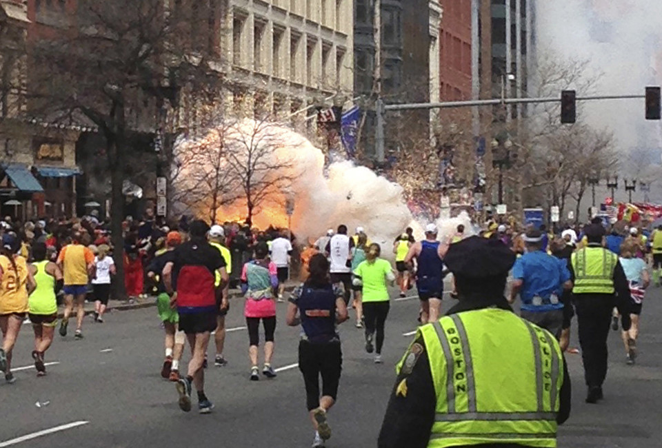 Runners continue to run towards the finish line of the Boston Marathon as an explosion erupts near the finish line of the race in this photo exclusively licensed to Reuters by photographer Dan Lampariello after he took the photo in Boston, Massachusetts, April 15, 2013. Two simultaneous explosions ripped through the crowd at the finish line of the Boston Marathon on Monday, killing at least two people and injuring dozens on a day when tens of thousands of people pack the streets to watch the world famous race.  REUTERS/Dan Lampariello  (UNITED STATES - Tags: CRIME LAW SPORT ATHLETICS) MANDATORY CREDIT - RTXYN2Q