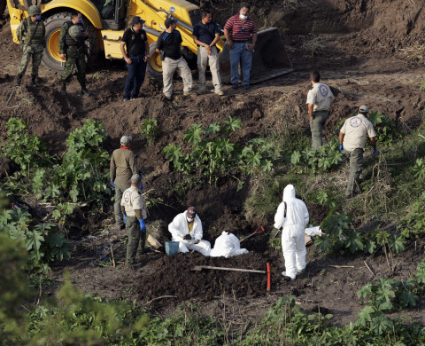 Forensic technicians search for human remains in a mass grave on the banks of the Lerma river in La Barca November 21, 2013. The number of murder victims unearthed in mass graves in La Barca, a small town to the west of Mexico, this month has risen to 34, as authorities extend investigations in a troubled region of the drug-ravaged country where cartels are battling each other for turf control. Picture taken November 21, 2013.  REUTERS/Alejandro Acosta (MEXICO  - Tags: CRIME LAW CIVIL UNREST) - RTX15OX3
