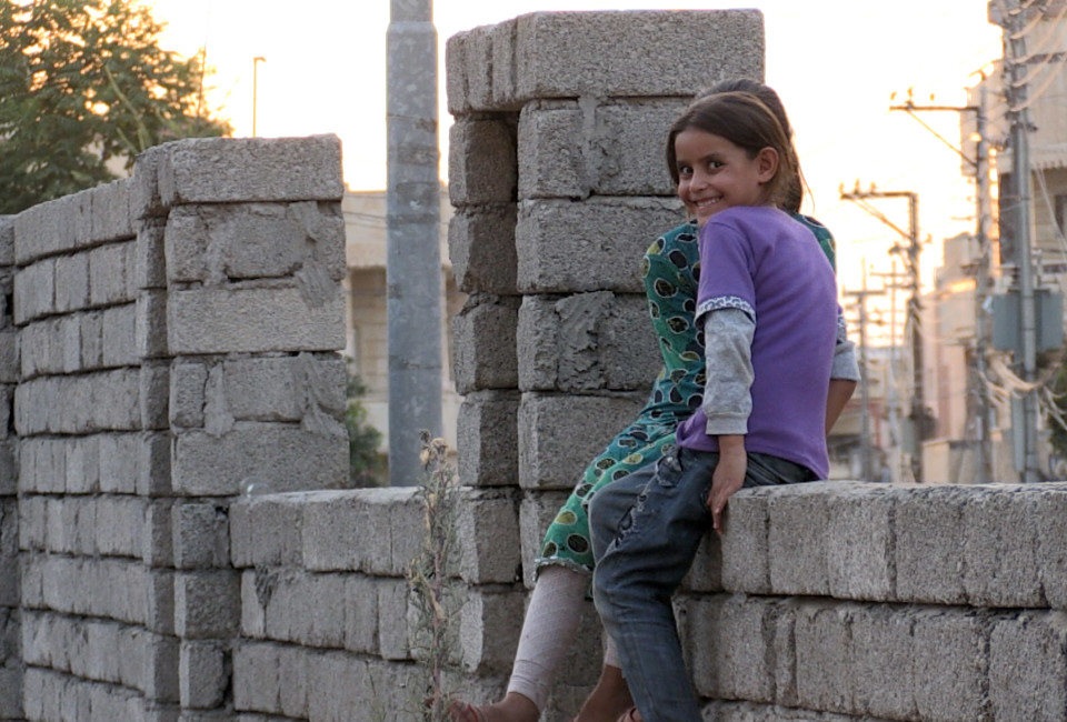 Two displaced Yazidi girls sit on a wall at a building site in the northern Iraqi town of Zakho. Entire villages of Yazidi, tens of thousands of people, fled to Iraqi Kurdistan after Islamic State militants took over their communities on the northern Nineveh plains.