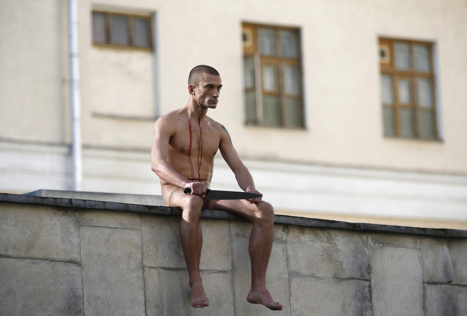 "Artist Pyotr Pavlensky sits on the wall enclosing the Serbsky State Scientific Center for Social and Forensic Psychiatry after he cut off a part of his earlobe during his protest action titled ""Segregation"" in Moscow October 19, 2014. Pavlensky protested against the usage of forensic psychiatry for politically motivated purposes. He cut off his earlobe to demonstrate how authorities could  ""cut off"" an unwanted individual from society by using psychiatric and medical diagnosis to forcefully send a person to a penitentiary hospital, according to Pavlensky."