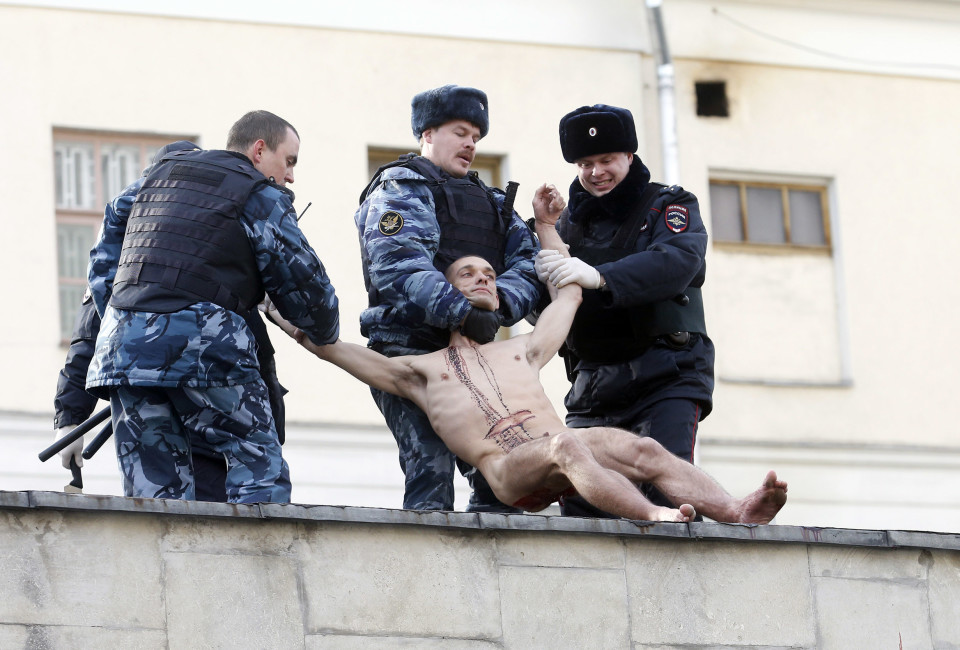"Interior Ministry members detain artist Pyotr Pavlensky after he cut off a part of his earlobe while sitting on the wall enclosing the Serbsky State Scientific Center for Social and Forensic Psychiatry during his protest action titled ""Segregation"" in Moscow October 19, 2014. Pavlensky protested against the usage of forensic psychiatry for politically motivated purposes. He cut off his earlobe to demonstrate how authorities could  ""cut off"" an unwanted individual from society by using psychiatric and medical diagnosis to forcefully send a person to a penitentiary hospital, according to Pavlensky."