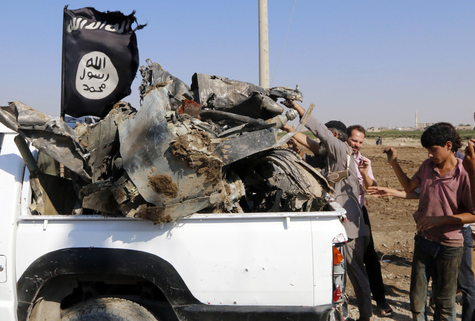 People load parts of the wreckage of a Syrian war plane onto a truck after it crashed in Raqqa, in northeast Syria. Islamic State fighters shot down the Syrian war plane using anti-aircraft guns on Tuesday, the first time the group has downed a military jet since declaring its cross-border caliphate in June, a group monitoring the civil war said.