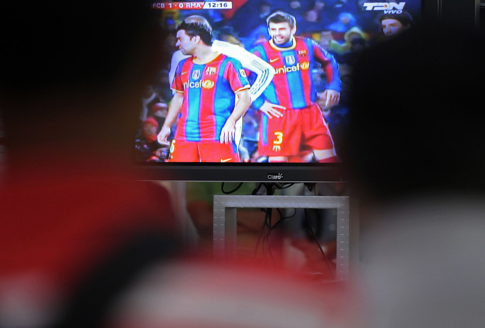 "Fans watch on TV the football match between Barcelona and Real Madrid, ""El Classico."""